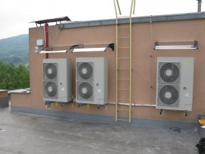 Venkovní jednotky na střeše panelového domu.